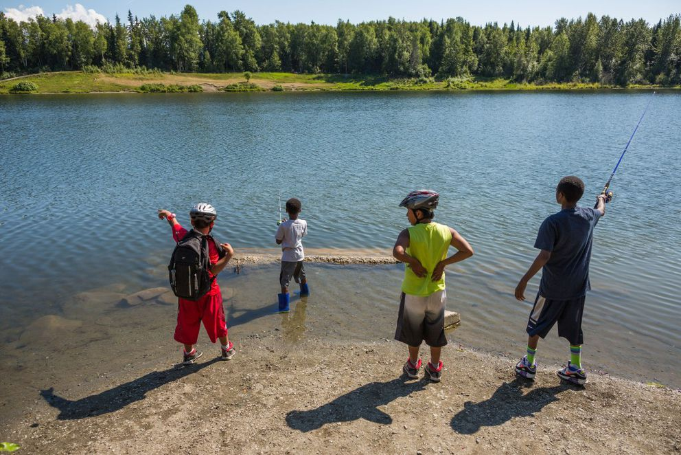 Fred Andrews, 9, left, and Josh Andrews, 12, second from right, coach Talon Copeland, 7, second from left, and TJ Copeland, 11, far right, as they fish for trout in Taku Lake on Friday, July 24, 2015. (Loren Holmes / Alaska Dispatch News)