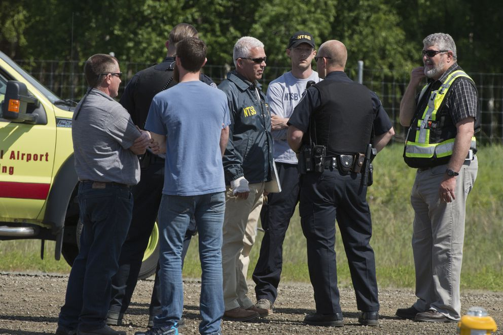 Clint Johnson, chief of the Alaska Regional Office of the National Transportation Safety Board, center, talks with police and others at the Lake Hood airstrip Wednesday afternoon. (Marc Lester / ADN)