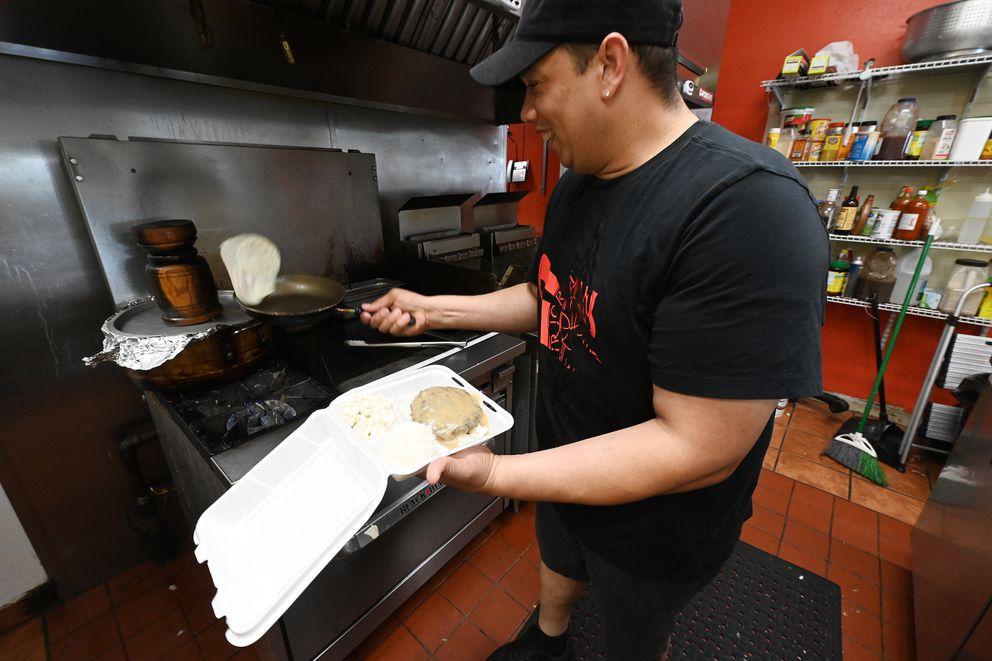 Owner Kelvin Guzman flips fried egg while preparing Moco Loco at Sunday's Loko Moko that serves Caribbean and Hawaiian cuisine off Boniface Parkway on Monday, June 7, 2021. (Bill Roth / ADN)