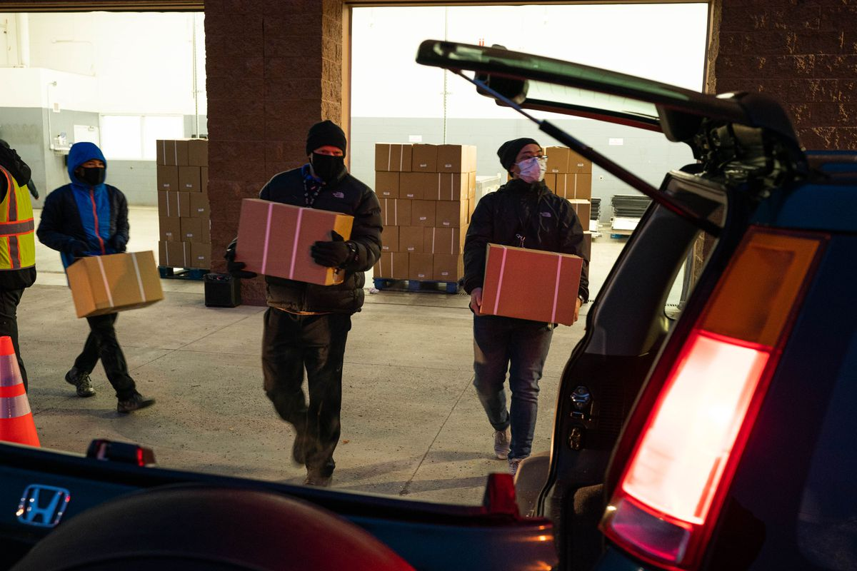 Volunteers Ross Connors, left, and Kurt Bleza load boxes of food into a vehicle at an emergency food distribution program run by the Food Bank of Alaska on Thursday, Nov. 5, 2020 at the former Sam's Club at Tikahtnu Commons in Anchorage. (Loren Holmes / ADN)