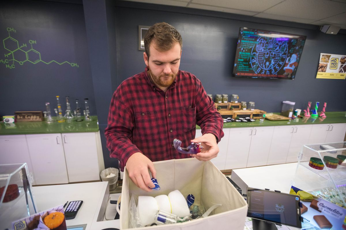 Cannabaska general manager Jake Warden holds broken glassware at the Anchorage cannabis shop on Wednesday, Dec. 5, 2018. Right after the earthquake, he launched a sale on glassware. (Loren Holmes / ADN)