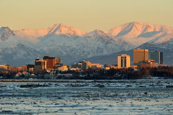 The setting sun lights up the Chugach Mountains and the Anchorage skyline as seen from Point Woronzof in Anchorage, Alaska on Wednesday, December 14, 2016. (Bob Hallinen / Alaska Dispatch News)