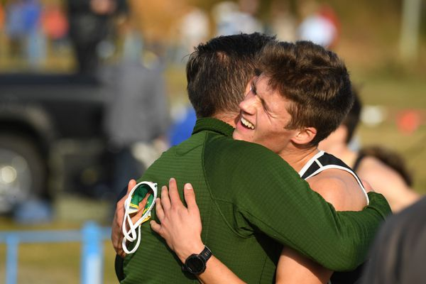 Alexander Maurer, of Service, gets a hug from. Coach after winning the division I boys in Alaska state cross country high school race at Kincaid Park in Anchorage, AK on Saturday, October 10, 2020. Maurer won with a time of 15:24. (Bob Hallinen)
