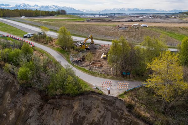 A man looks over the edge of the bluff at Point Woronzof on Tuesday, May 14, 2019. The bluff has been eroding for many years and is encroaching on the popular Tony Knowles Coastal Trail and nearby road. The Ted Stevens Anchorage International Airport, behind, is expanding the runway and adding additional navigation lights. (Loren Holmes / ADN)