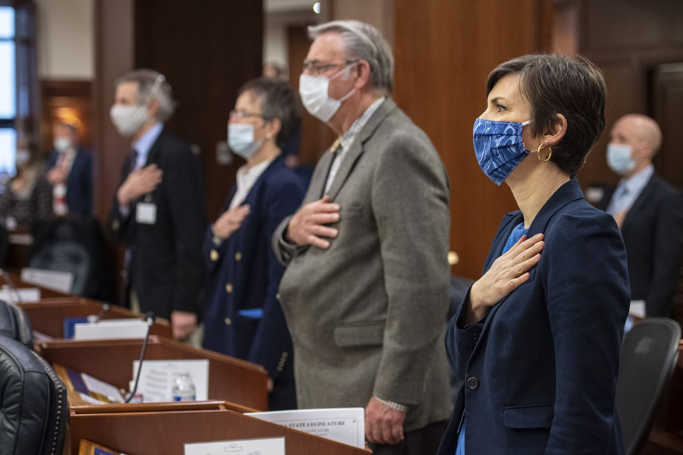 Alaska Representatives, including, from right to left: Ivy Spohnholz, D-Anchorage, Mel Gillis, R-Anchorage, Sarah Vance, R-Homer, Matt Claman, D-Anchorage, recite the Pledge of Allegiance as legislators return to the Capitol in Juneau on Monday, May 18, 2020, under new health mandates as they consider Gov. Mike Dunleavy's proposed use of federal Covid-19 money. (Photo by Michael Penn)