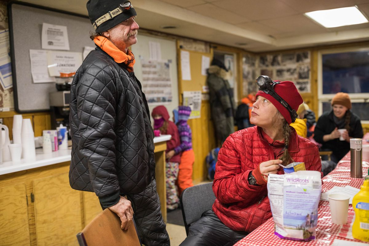 Aliy Zirkle and her husband, fellow musher Allen Moore, eat dinner at the Takotna checkpoint on Wednesday, March 7, 2018. (Loren Holmes / ADN)