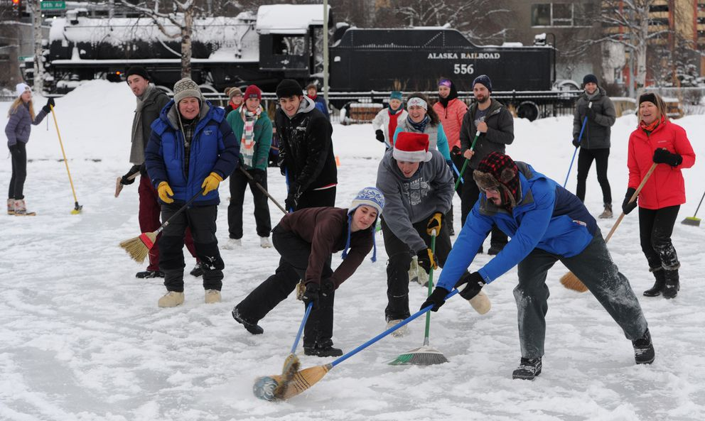 Nearly two dozen people played broom ball at the Delaney Park Strip near downtown Anchorage on Christmas Day, Dec. 25, 2019. Teresa Zimmer, right, said the Christmas Day tradition 'started years ago when our kids were young. ' Diana Radoff said 'basically it started with a bunch of little kids and now they're all in college. It's a way for them all to touch base, a little reunion during the holidays, and it gets us all out of our pajamas on Christmas. ' (Bill Roth / ADN)