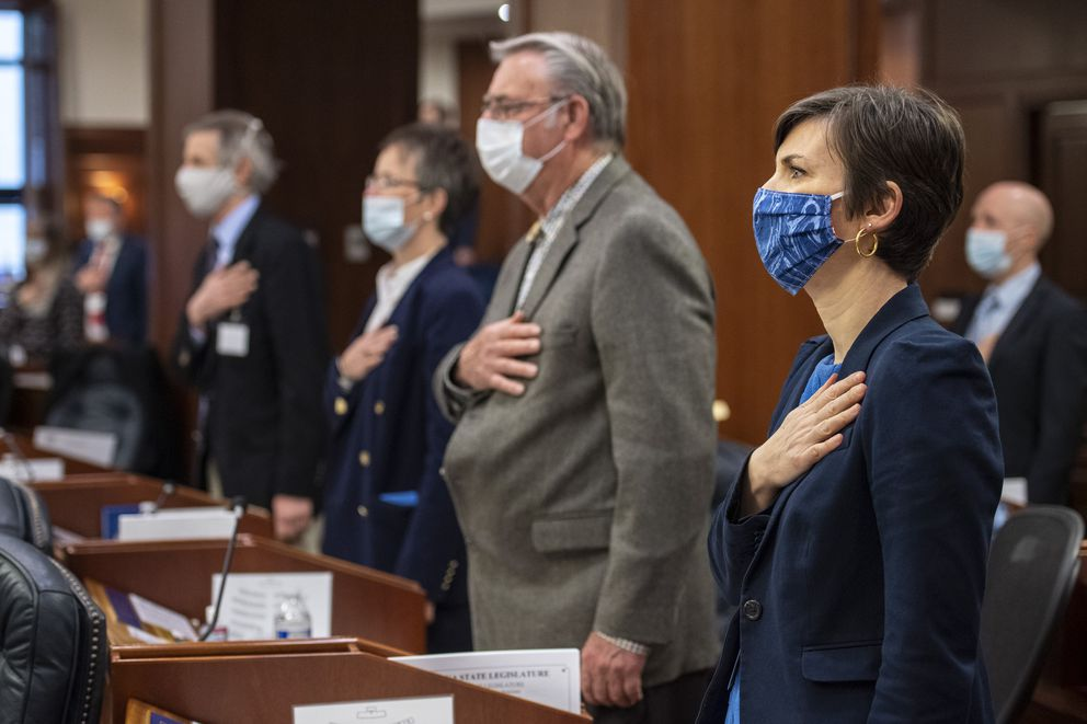 From right, Alaska state Reps. Ivy Spohnholz, D-Anchorage, Mel Gillis, R-Anchorage, Sarah Vance, R-Homer, and Matt Claman, D-Anchorage, recite the Pledge of Allegiance as legislators return to the Capitol in Juneau on May 18, 2020, under new health mandates. (Photo by Michael Penn)