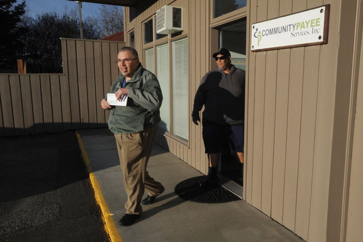 Ron Barlip picked up a benefit check at Community Payee Services in Spenard on Tuesday with the help of Tony Lopez, a direct support professional at HOPE Community Resources. (Bill Roth / ADN)