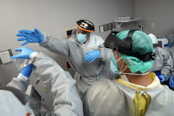 Dr. Joseph Varon, center, reaches for an IV bag inside the Coronavirus Unit at United Memorial Medical Center, Monday, July 6, 2020, in Houston. Varon says he has worked more than 100 days with barely a rest and normally sleeps just a few hours a night. (AP Photo/David J. Phillip)