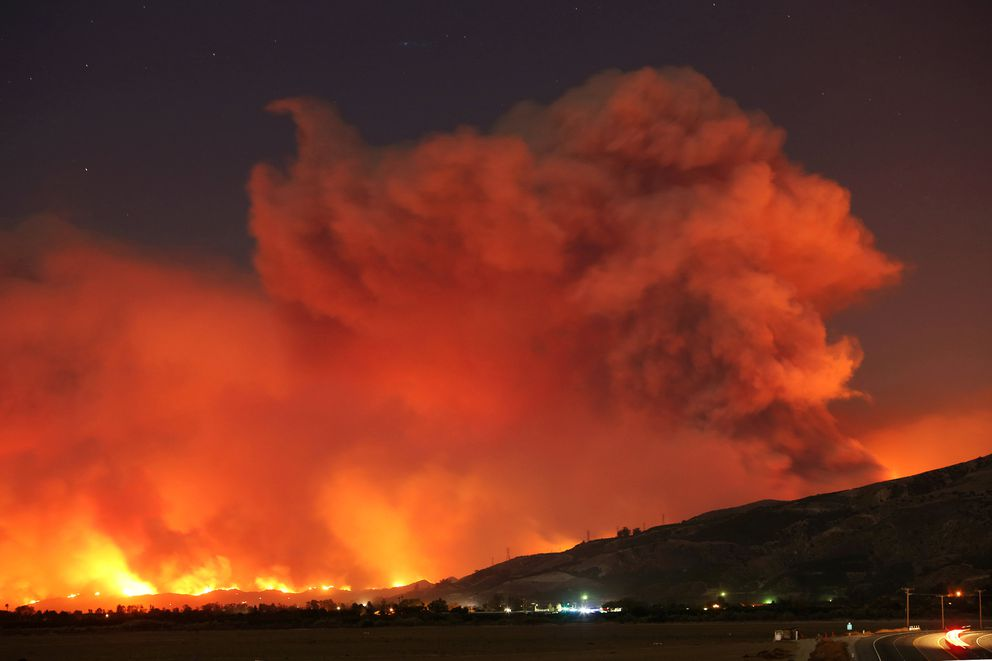 Smoke rises into the night sky as strong winds push the Thomas Fire across thousands of acres near Santa Paula, California. REUTERS/David McNew