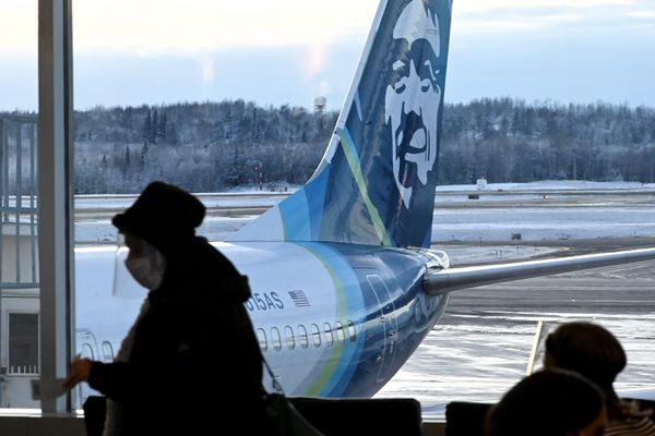 An air traveler wearing a face covering and shield waits to board an Alaska Airlines flight at Ted Stevens Anchorage International Airport on Thursday, Nov. 19, 2020. (Bill Roth / ADN)