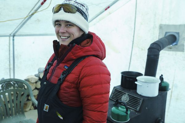Head Yukon Quest veterinarian Cristine Hansen of Fairbanks smiles in the vet tent at Dawson City. Yukon Quest vets inspect every dog in the race at least four times between the start and finish. Hansen started volunteering for the Yukon Quest in 2010, and is serving as head vet for her fourth year. Feb. 7, 2018. (Robin Wood / Fairbanks Daily News-Miner)
