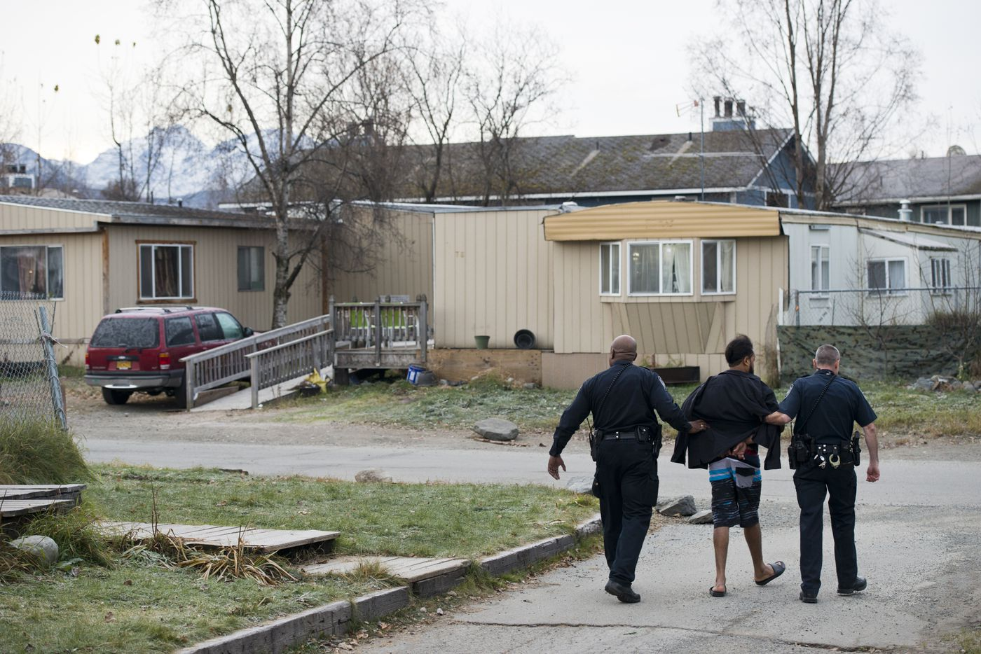 Anchorage Police warrants officers Troy Leonard, visible, and Aaron Roberts arrest Jose Contreras Evangelista at an East Anchorage home. Police say Evangelista fired a gun at a vehicle several times, resulting in two felony assault charges and a weapon misconduct charge. (Marc Lester / Alaska Dispatch News)