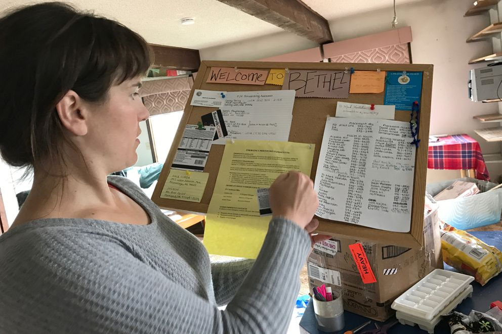 Chelsea Gulling, a former Jesuit volunteer in Bethel, suggests the group take the list of phone numbers but ditch the rest of the bulletin board materials during a move to a new house July 15. (Lisa Demer / Alaska Dispatch News)
