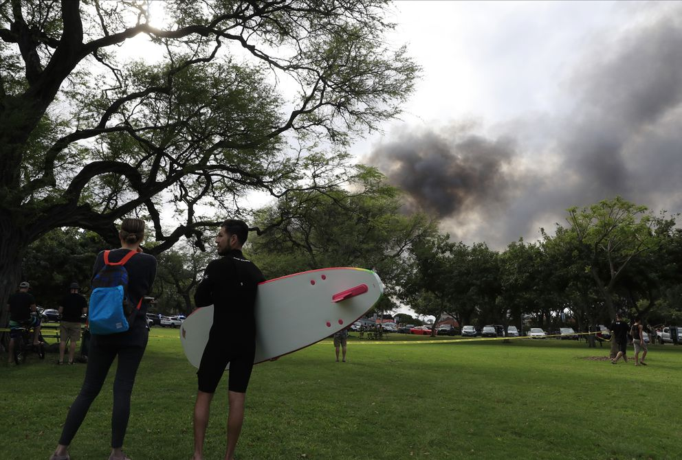 Aina Haina resident Kai Ohashi, right, and Waikiki resident Lucy Taylor observe billowing smoke from a house fire after a shooting and domestic incident at a residence on Hibiscus Road near Diamond Head on Sunday, Jan. 19, 2020, in Honolulu. Witnesses say at least two Honolulu police officers were shot and two civilians were injured. Moments after the shooting, the house was set on fire, possibly by the suspect. (Jamm Aquino/Honolulu Star-Advertiser via AP)