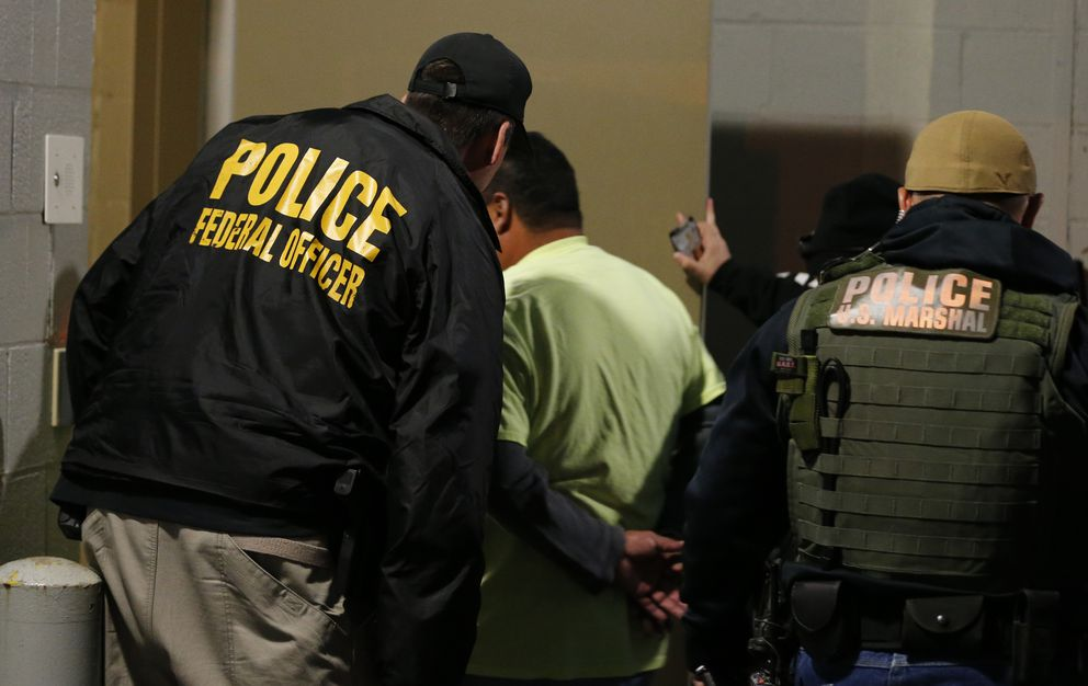 FILE - In this Oct. 22, 2018, file photo U.S. Immigration and Customs Enforcement agents escort a target to lockup during a raid in Richmond, Va. (AP Photo/Steve Helber, File)