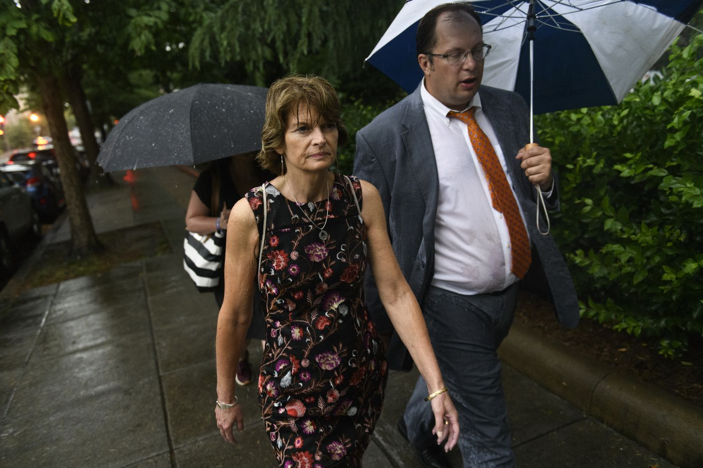 Sen. Lisa Murkowsk walks home through the rain while talking with her chief of staff Micheal Pawlowski on June 18, 2019. (Marc Lester / ADN)