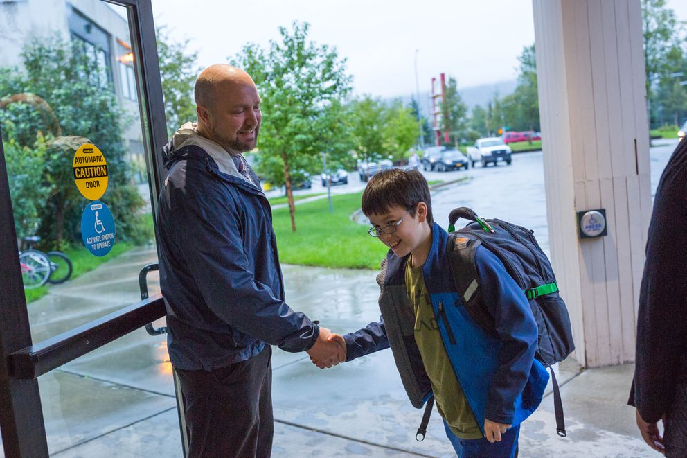 STrEaM Academy Principal Adam Mokelke greets 11-year-old Porter Hiett on the second day of school. (Loren Holmes / Alaska Dispatch News)