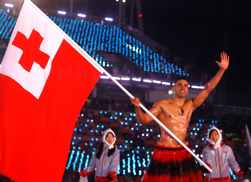 Pita Taufatofua of Tonga, competing in cross-country skiing, carries the national flag. REUTERS/Kai Pfaffenbach