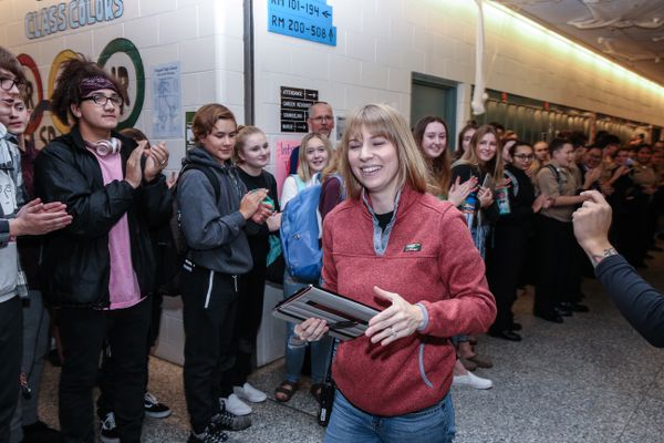 Ashley Bailey gets cheered on by students and faculty at Chugiak High on Oct. 17. Bailey is a security guard at the school who recently took leave to undergo treatment for breast cancer. On her last day, students and teachers lined the halls to lend her their support. (Photo by Scott Minor / Fitzgerald Photography)