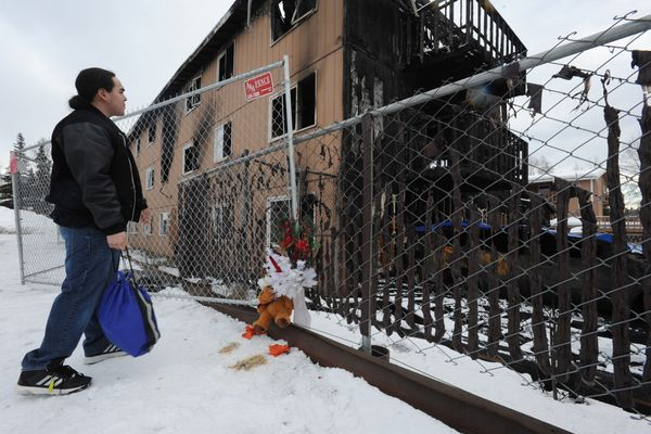 Kenneth Towksjhea pays his repects to Royal Suite Apartments fire victims on Thursday, Feb. 16, 2017. (Bill Roth / Alaska Dispatch News)