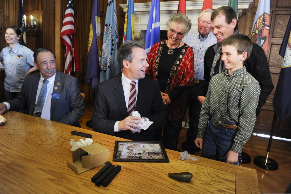 In this April 16, 2019, file photo, Luke Phipps, 12, presents Montana Gov. Steve Bullock with a fossilized rib and tail vertebrae from a triceratops at the state Capitol in Helena, Mont., after the governor signed a bill to clarify that fossils are part of a property's surface rights, not its mineral rights, unless a contract separating the ownership says otherwise. (Thom Bridge/Independent Record via AP)