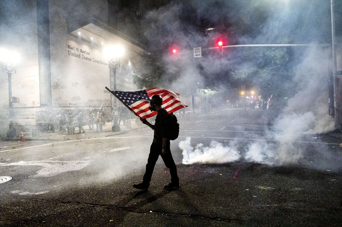 A Black Lives Matter protester carries an American flag as teargas fills the air outside the Mark O. Hatfield United States Courthouse on Tuesday, July 21, 2020, in Portland, Ore. (AP Photo/Noah Berger)