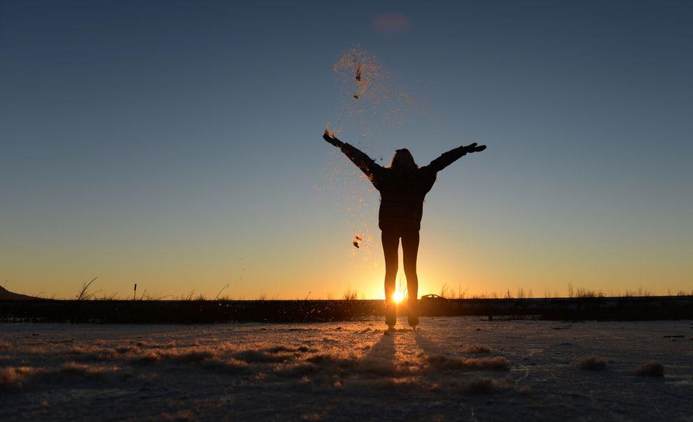 Abigail Thomas throws cattail fluff into the air as the sun sets at Potter Marsh (Bob Hallinen / ADN)