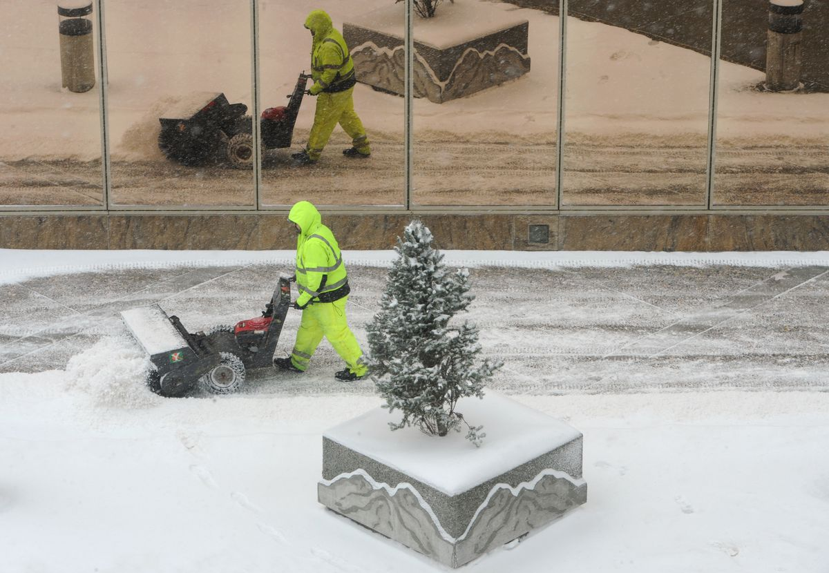 A worker sweeps the sidewalks in downtown Anchorage during the snowstorm on Monday. (Bill Roth / ADN)