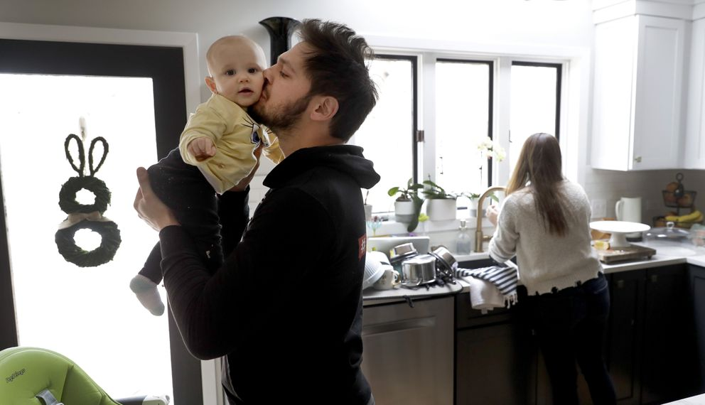 Former NHL player Dan Carcillo kisses his daughter Scarlett as his wife Ela works in the kitchen at their rural home in Homer Glen, Ill. (AP Photo/Charles Rex Arbogast)