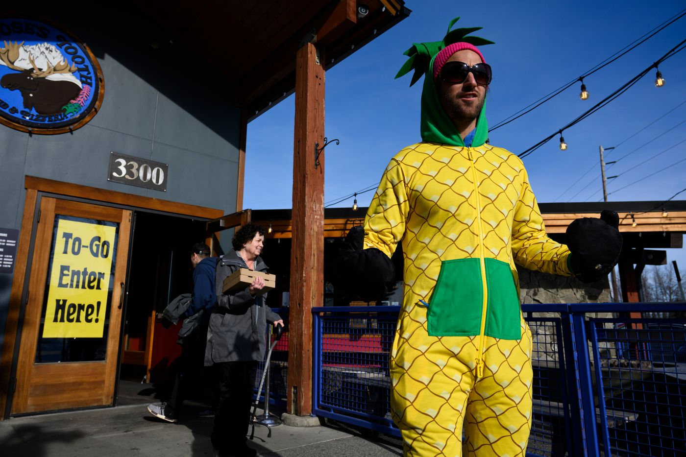 """Moose's Tooth bartender Josh Bleznak wears a pineapple costume and works as a doorman at the Midtown Anchorage restaurant on Friday, March 20, 2020. Bleznak's job is to keep the flow customers picking up orders to five at a time inside the restaruant. He also said he hopes to make people smile. """"Let's have people enjoy themselves in a time that kind of sucks,"""" Bleznak said. (Marc Lester / ADN)"""