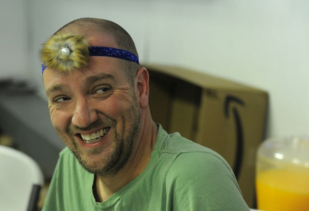 A member of the Iditarod trail crew, Joe Hauhn from Charleston, S.C., models the headband he bought for his 4-year-old daughter Julianne Hauhn from Darlene Nicholia at the checkpoint in Tanana. Hauhn purchased gifts for his wife and other daughter and a Christmas ornament. (Bob Hallinen / Alaska Dispatch News)