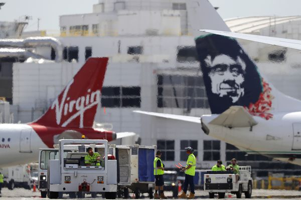 Ramp workers stand between a Virgin America plane, left, and an Alaska Airlines plane, right, Tuesday, April 24, 2018, at Seattle-Tacoma International Airport in Seattle. After Tuesday, the two airlines will merge their passenger-service systems and on Wednesday, travelers at U.S. airports served by Virgin America are expected to only see Alaska signage and branding at ticketing and gate areas following an overnight changeover. (AP Photo/Ted S. Warren)