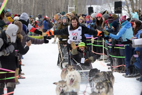 Jeremy Keller reaches out for hand slaps while running his team through the Trailgate party along the Iditarod ceremonial start route, March 7, 2020. (Anne Raup / ADN)