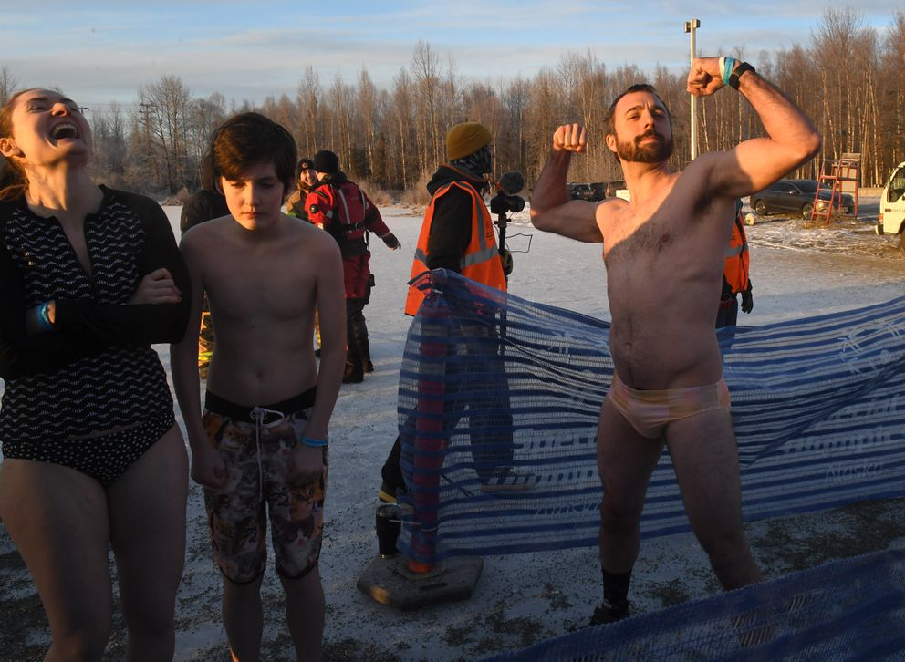 Lyndsay Kotalik laughs as Greg Rowland strikes a pose before they jump into the icy waters of Goose Lake in Anchorage, AK on Saturday, December 21, 2019. The two and Ben Weaver in the middle were participating in the 11th annual Special Olympics Polar Plunge. (Photo by Bob Hallinen)