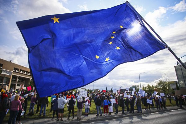 A man waves an Alaska flag to passing cars while standing on the median on E. 36th Avenue as people gather outside the Z. J. Loussac Public Library to attend a protest on Aug. 11, 2020. (Emily Mesner / ADN)