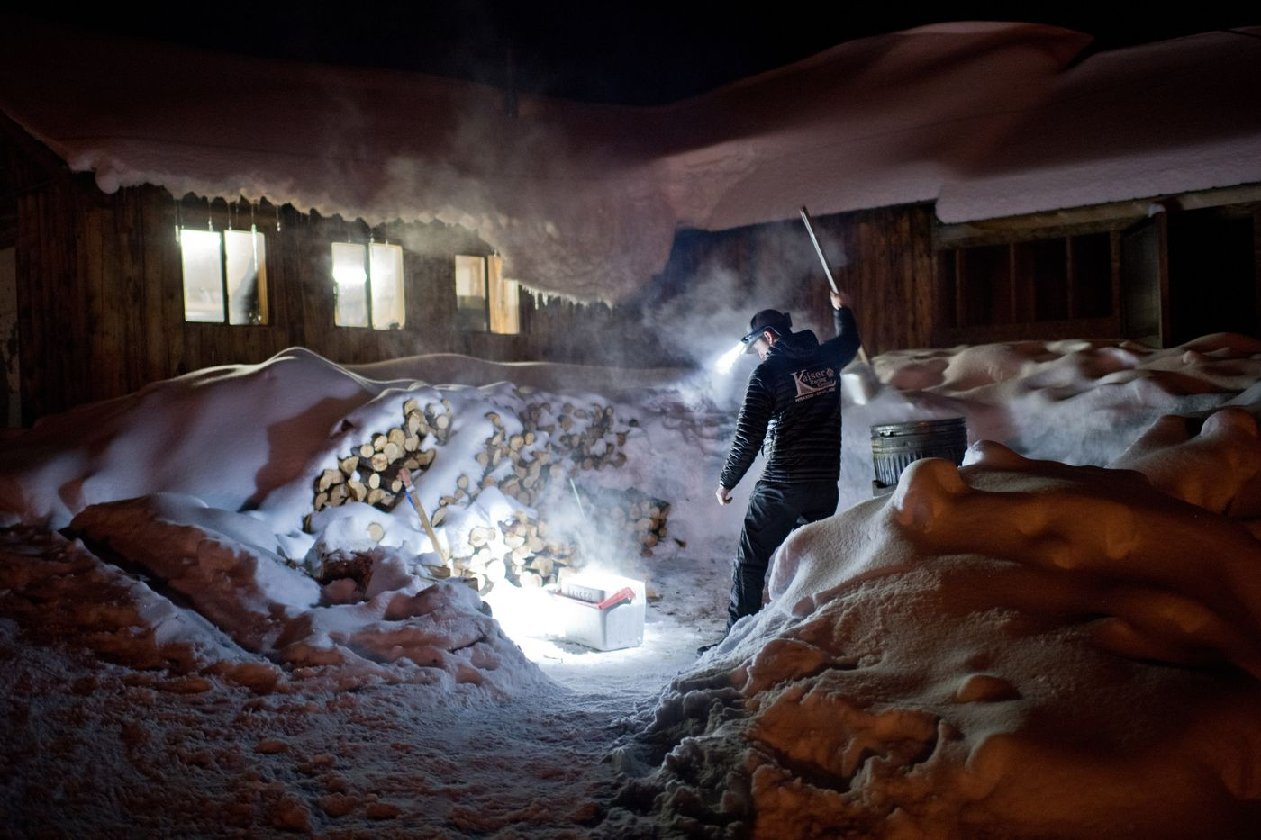 Peter Kaiser scoops hot water in Takotna on March 6. (Marc Lester / ADN)