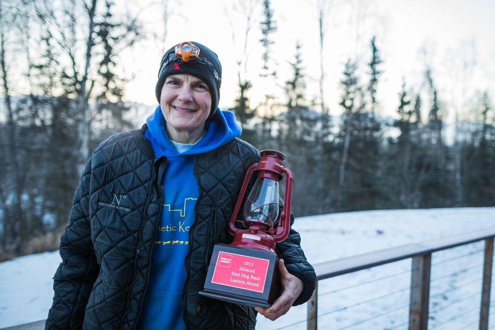 Iditarod musher Christine Roalofs with her 2013 Iditarod red lantern on Friday, February 27, 2015. (Loren Holmes / ADN)