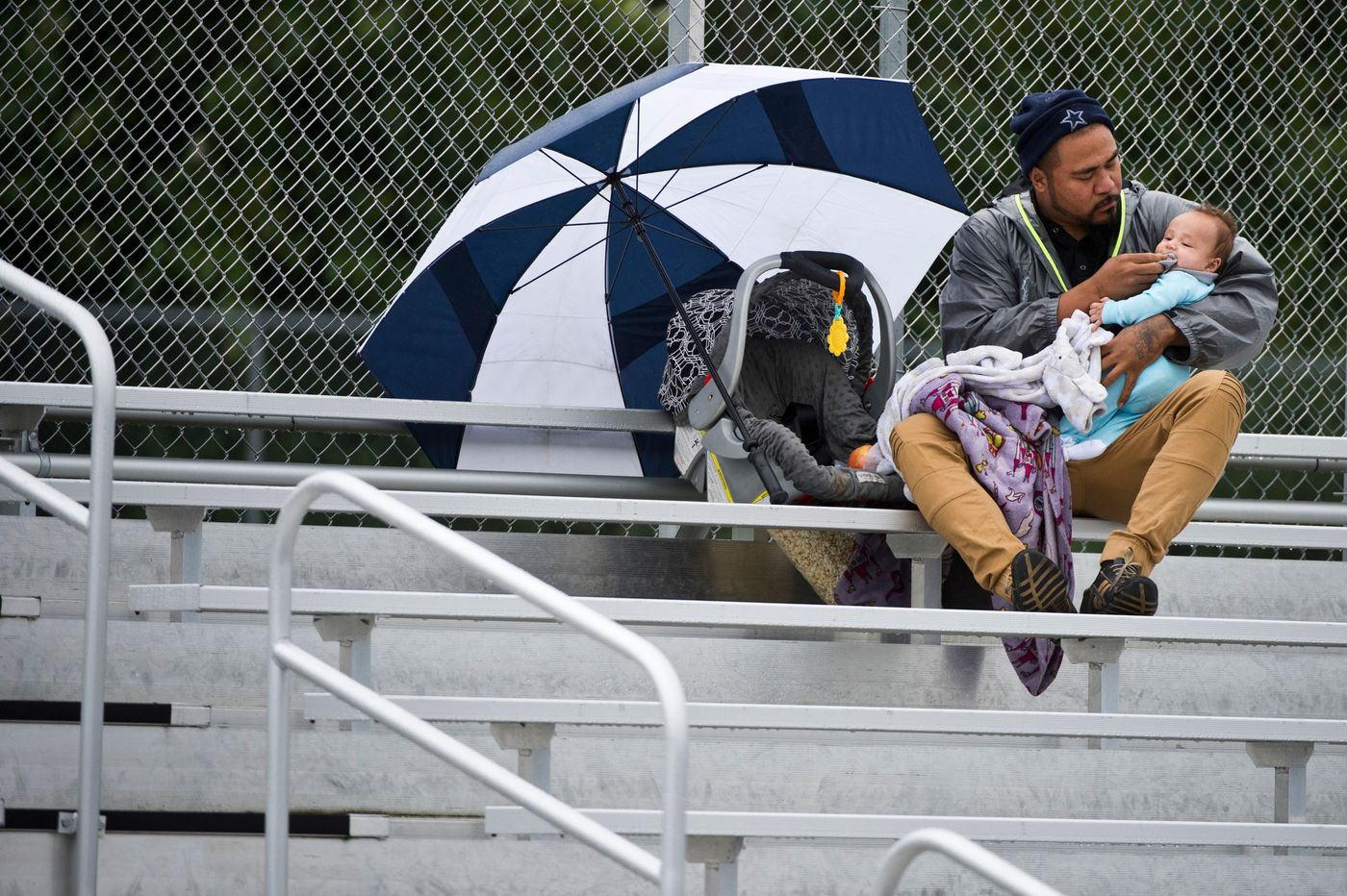 Anthony Pereira holds his son Alex Pereira while taking in the Greatland Packers and Eagle River Broncos game on Aug. 26, 2018. (Marc Lester / ADN)