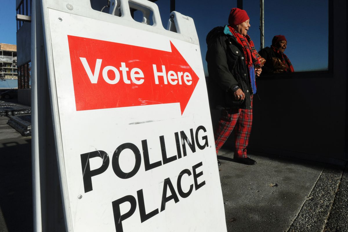 Voter Odelma Holmes walks towards the state Division of Elections office at 2525 Gambell Street on Oct. 22, 2014.
