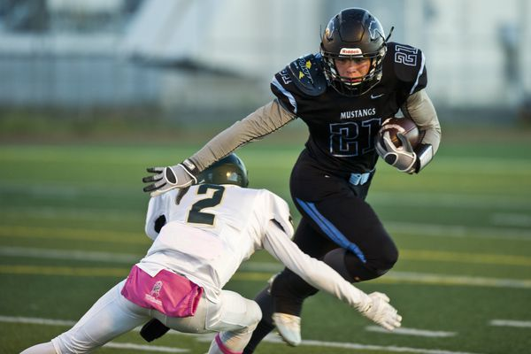Chugiak's Derryk Snell tries to escape a tackle by Service's Leslie Harris in the first quarter. Chugiak hosted Service in the first rounds of large schools football state championship playoffs on Friday, October 7, 2016. (Marc Lester / Alaska Dispatch News)