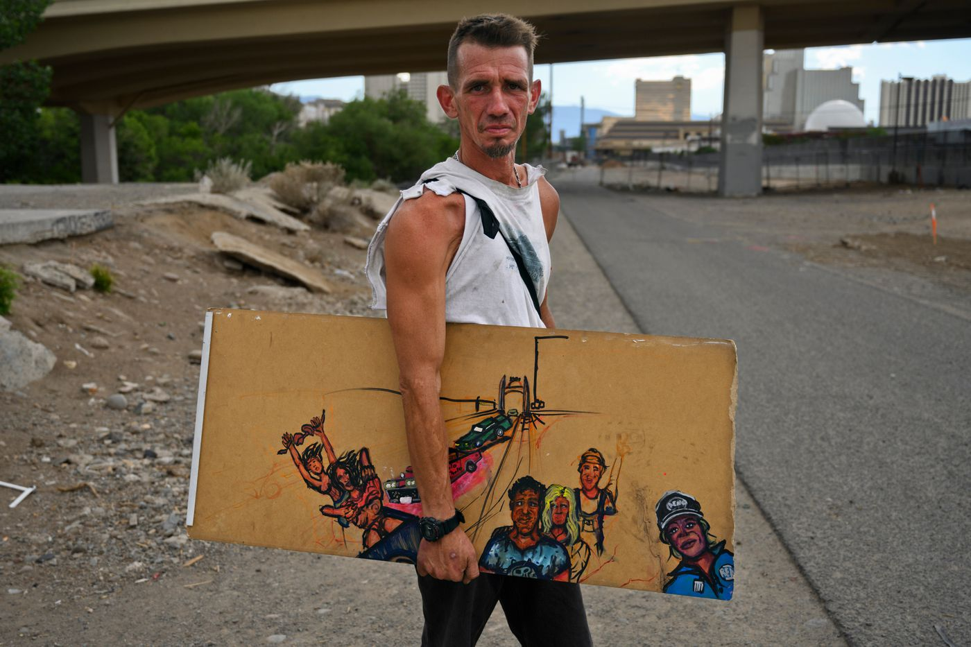 Matthew Tittor holds his artwork near the Wells Avenue Bridge over the Truckee River on June 23, 2021. The area was the site of a large homeless encampment before it was cleared by the city. Tittor, who camped nearby, said he had no interest in staying at the Nevada CARES Campus. (Marc Lester / ADN)