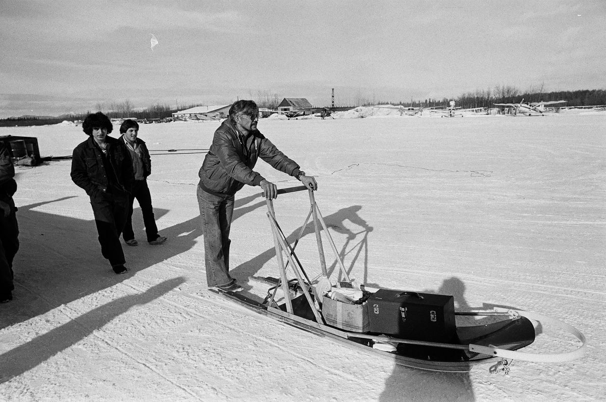 George Attla pushes a sled at the McGrath checkpoint during the 1981 Iditarod. He was on the trail in support of his son, Gary Attla, who was running that year's Iditarod. (Marc Olson / ADN archive)