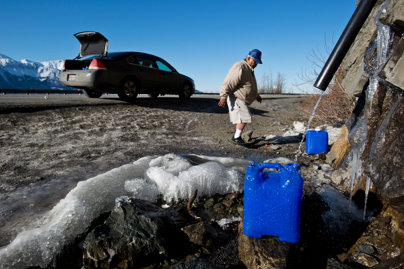 Willie Thomas carefully steps across ice spots in the ditch along the Seward Highway as he fills four large jugs last month. He said he doesn't have a problem with tap water, but prefers the taste of water from the highway pipe. (Marc Lester / Alaska Dispatch News)