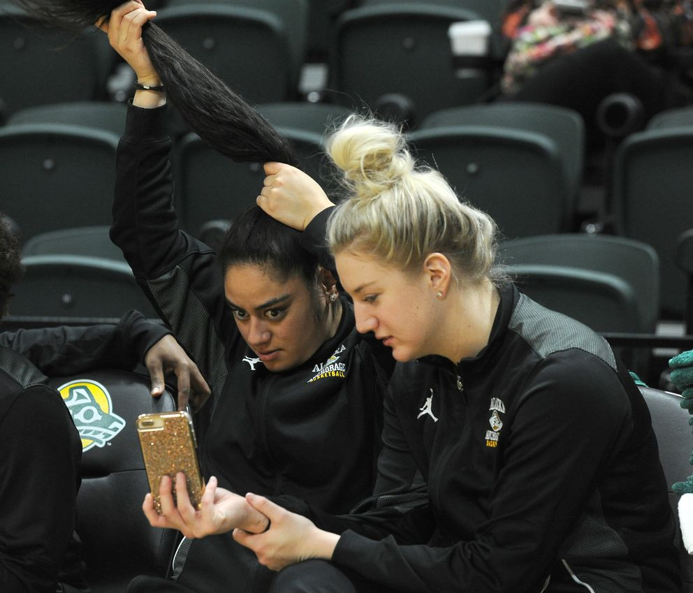 UAA's Shelby Cloninger, right, holds a phone so teammate Victoria Langi can fix her ponytail during the game. Cloninger, the team's leading scorer, sat out with an injury and Langi is a redshirt. (Bob Hallinen / ADN)