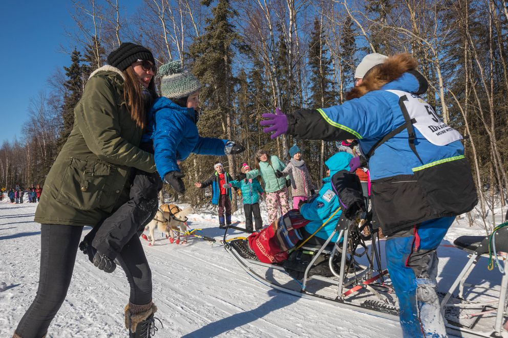 Alyssa Ament helps Maclen Kilheffer, 2, get a high five from Alabama musher Seth Barnes at University Lake during the ceremonial start of the 2017 Iditarod. (Loren Holmes / ADN)