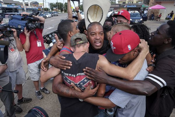 Ty Hardaway, 44, of Dallas is in the center of a group hug after some marchers from Black Lives Matter had a meeting with counterprotest group supporting Blue Lives Matter. The two groups stood on separate sides of a busy intersection and ultimately came to an understanding. (Bonnie Jo Mount / The Washington Post)