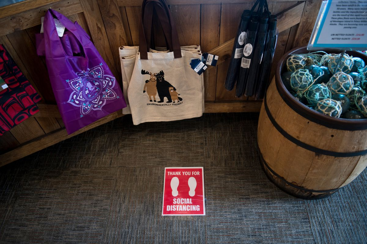 A notice on the floor of Grizzly Gifts reminds customers to space apart near the cash register on April 27, 2020. (Marc Lester / ADN)