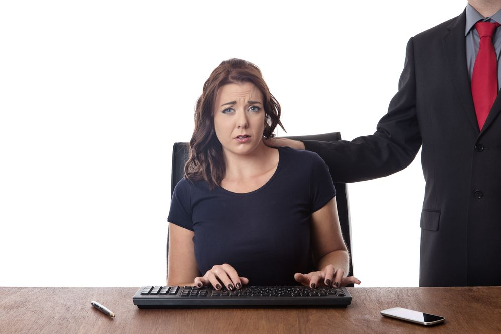 business woman sitting at her desk with a male work colleague touching her on the shoulder sexual harassment (Thinkstock)